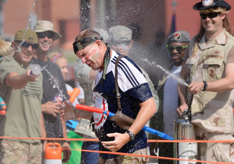 Col. David Burgy, 138th Fighter Wing Commander, gets soaked with water as he completes the obstacle course during the 138th Fighter Wing's combat dining-in held Aug. 1, 2015 at the Tulsa Air National Guard base.  The wing's senior non-commissioned officer's council sponsored the event as a way to enhance camaraderie and promote esprit de corps throughout the ranks.   (U.S. National Guard photo by Master Sgt. Mark A. Moore/Released)