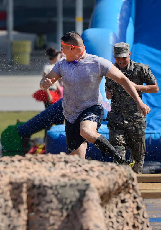 Staff Sgt. Alan Williams, 138th Fighter Wing Chaplains Assistant, runs from people trying to soak him on the obstacle course during the 138th Fighter Wing's combat dining-in held Aug. 1, 2015 at the Tulsa Air National Guard base.  The wing's senior non-commissioned officer's council sponsored the event as a way to enhance camaraderie and promote esprit de corps throughout the ranks.   (U.S. National Guard photo by Master Sgt. Mark A. Moore/Released)