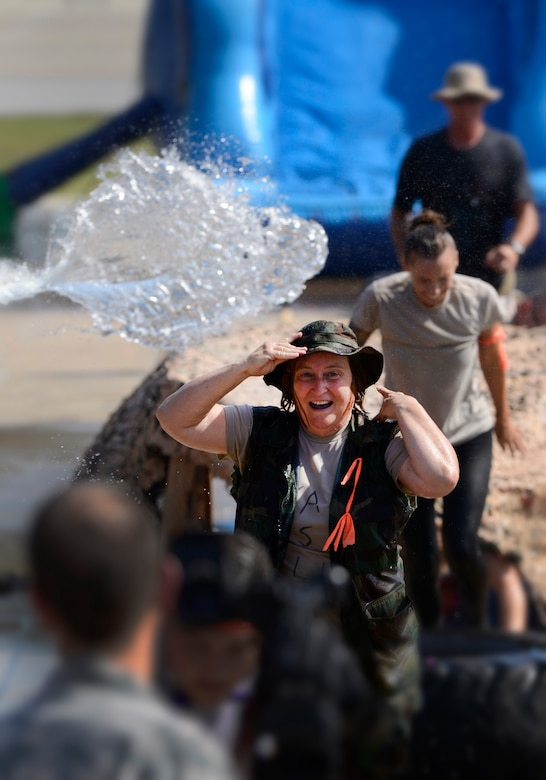 Master Sgt. Jerry Shaffer, 138th Logistics Readiness Squadron, is doused with water while running the obstacle course during the 138th Fighter Wing's combat dining-in held Aug. 1, 2015 at the Tulsa Air National Guard base.  The wing's senior non-commissioned officer's council sponsored the event as a way to enhance camaraderie and promote esprit de corps throughout the ranks.   (U.S. National Guard photo by Master Sgt. Mark A. Moore/Released)