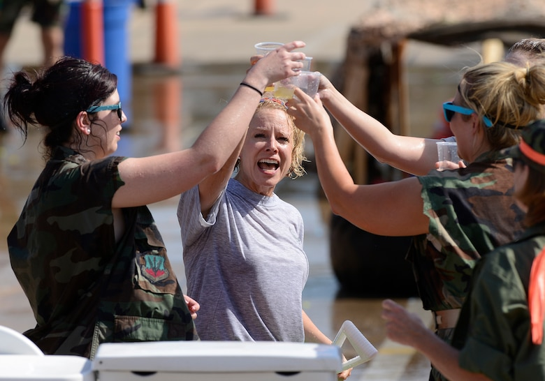 Upon completing the obstacle course, Lt. Col. Ginger Turcotte, 138th Force Support Squadron Commander, toasts her airmen with a refreshing non-alcoholic beverage from the grog during the 138th Fighter Wing's combat dining-in held Aug. 1, 2015 at the Tulsa Air National Guard base.  The wing's senior non-commissioned officer's council sponsored the event as a way to enhance camaraderie and promote esprit de corps throughout the ranks.   (U.S. National Guard photo by Master Sgt. Mark A. Moore/Released)