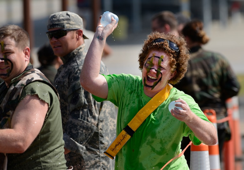 Tech. Sgt. Sarah Vroman, 138th Comptroller Flight, tosses water balloons at obstacle course participants during the 138th Fighter Wing's combat dining-in held Aug. 1, 2015 at the Tulsa Air National Guard base.  The wing's senior non-commissioned officer's council sponsored the event as a way to enhance camaraderie and promote esprit de corps throughout the ranks.   (U.S. National Guard photo by Master Sgt. Mark A. Moore/Released)