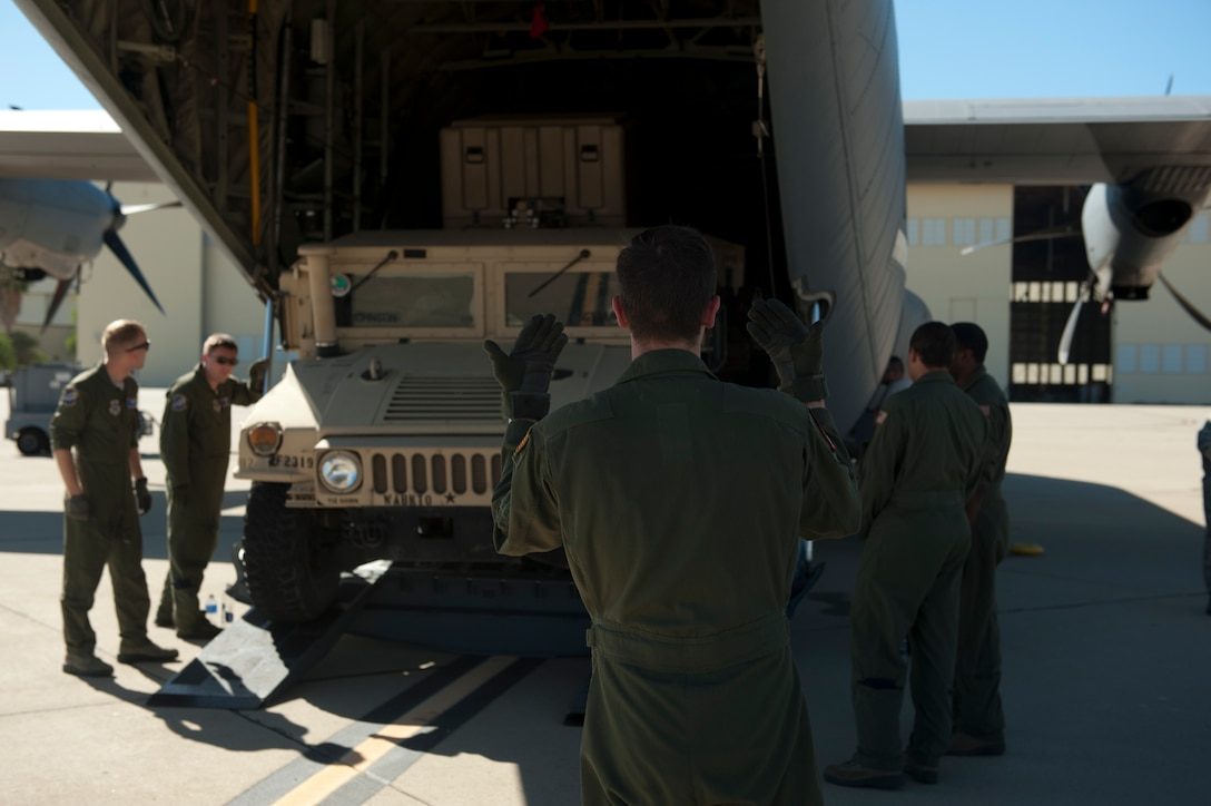 Senior Airman William Rush, a 41st Airlift Squadron loadmaster, marshals a Humvee into a C-130J Aug. 4, 2015, at March Reserve Air Force Base, Calif. The 41st AS was taking part in Operation Dragon Spear, a joint operations access exercise where their mission was to support large formation operations by providing C-130 Combat Airlift with Army assets. (U.S. Air Force photo by Senior Airman Scott Poe)
