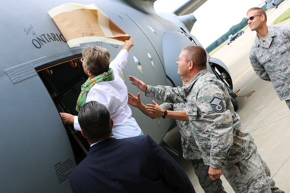 "Beverly Collins reveals the ""Spirit of Ontario"" as members of the 179th Airlift Wing, Mansfield, Ohio, gathered for the dedication of one of their C-130H Hercules, the ""Spirit of Ontario"", Aug. 6, 2015. This aircraft is one  of eight C-130H's that have been assigned to the Ohio Air National Guard unit. Each of the eight aircraft are being dedicated to supportive local communities.  Special guests included Ontario Mayor Randy E. Hutchinson, Service Safety Director Jeff Wilson, Ontario Council President Larry Collins and his wife Beverly. (U.S. Air National Guard photo by Tech. Sgt. Joe Harwood\Released)"
