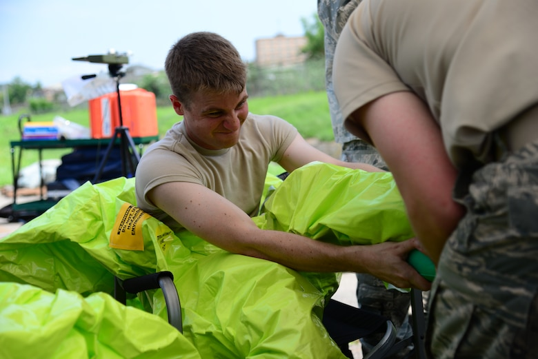 "Airman 1st Class Benjamin Thompson, 51st Civil Engineer Squadron emergency management apprentice, is assisted in donning his level A chemical, biological, radiological and nuclear protection suit during an integrated base emergency response capability training exercise at Osan Air Base, Republic of Korea, Aug 4, 2015. The level A CBRN suit is a fully encapsulated ensemble, with a self-contained breathing apparatus, used to respond to ""all-hazards"" situations.