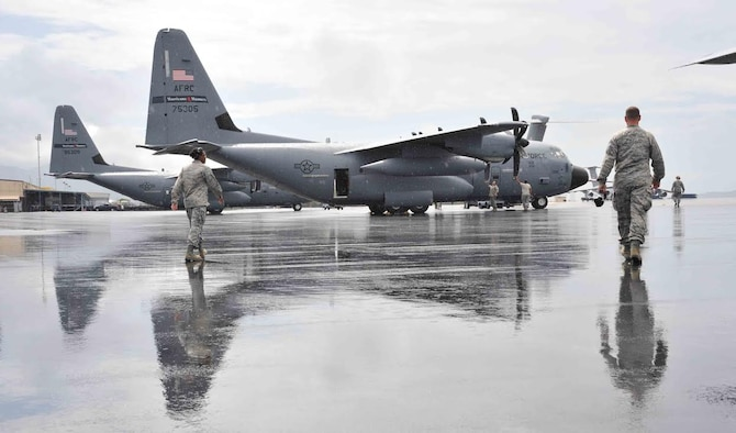 Maintenance members with the 403rd Maintenance Group walk out to recover a WC-130J following a weather reconnaissance mission (U.S. Air Force file photo/Maj. Marnee A.C. Losurdo)