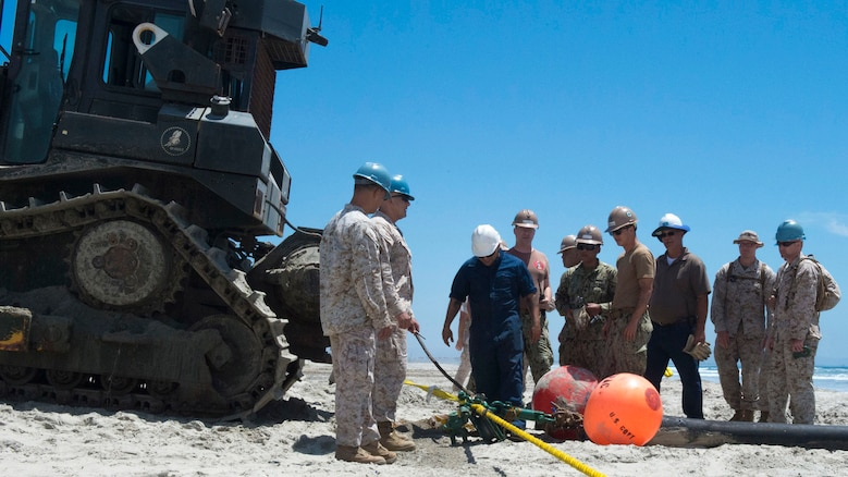 Marines with Bulk Fuel Co., 1st Marine Logistics Group, team up with Sailors from Amphibious Construction Battalion 1 to perform a beach unloading exercise using the Beach Termination Unit, in Coronado, California, Aug. 1-4, 2015.  Approximately 30 Marines with Bulk Fuel Company, 7th Engineer Support Battalion, 1st Marine Logistics Group, teamed up with Sailors from Amphibious Construction Battalion 1 to conduct a beach unloading exercise. What made the training unique was the use of the BTU, which allows Marines to transfer fuel from a ship out in the ocean to Marines on land.