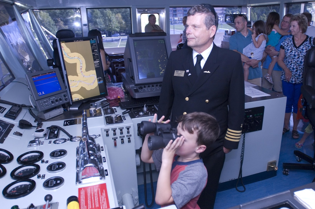 Motor Vessel Mississippi Captain Lee Hendrix watches as Garrett Durrett, 5, of Pelham, Ala., looks through a pair of binoculars during a public tour of the vessel docked at Ross's Landing in Chattanooga, Tenn., Aug. 7, 2015. The M/V Mississippi spends more than 90 percent of its time as a working towboat, moving barges, equipment and supplies on the lower Mississippi River.  The M/V Mississippi, built in 1993 by Halter Marine, is the fifth Army Corps of Engineers towboat to bear the name.  It is the largest diesel towboat in the United States at 241-feet long, 58-feet wide and five stories high.  Three 2,100-horsepower diesel engines power the vessel.