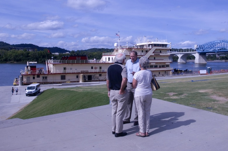 Jimmy Waddle (Center), U.S. Army Corps of Engineers Nashville District Engineering and Construction Division chief, encourages a couple to board the Motor Vessel Mississippi to enjoy a public tour of the vessel docked at Ross's Landing in Chattanooga, Tenn., Aug. 7, 2015. The M/V Mississippi spends more than 90 percent of its time as a working towboat, moving barges, equipment and supplies on the lower Mississippi River.  The M/V Mississippi, built in 1993 by Halter Marine, is the fifth Army Corps of Engineers towboat to bear the name.  It is the largest diesel towboat in the United States at 241-feet long, 58-feet wide and five stories high.  Three 2,100-horsepower diesel engines power the vessel.