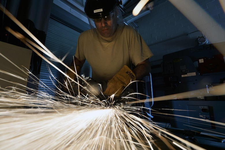 Master Sgt. Jim Vlacich, a machinist with the 106th Rescue Wing metal technologies shop, grinds down a section of metal at Francis S. Gabreski Air National Guard Base, N.Y., Aug. 6, 2015. Aircraft metals technology specialists are responsible for machining parts, welding, creating items from scratch and welding parts necessary for keeping the 106th RQW's aircraft flying. (U.S. Air National Guard photo/Staff Sgt. Christopher S. Muncy)