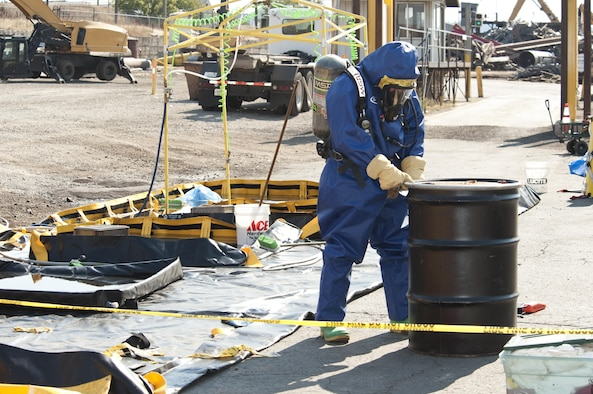 Senior Airman Nicholas Bouselli, a 92nd Civil Engineer Squadron emergency management journeyman, approaches a metal drum containing the clothes of those directly exposed to a chlorine gas leak Aug. 12, 2015, at Pacific Steal and Recycling in Spokane, Wash. More than 25 people felt the effects of the chemical leak and have since been treated by medical responders. (U.S. Air Force photo/Airman Sean Campbell)