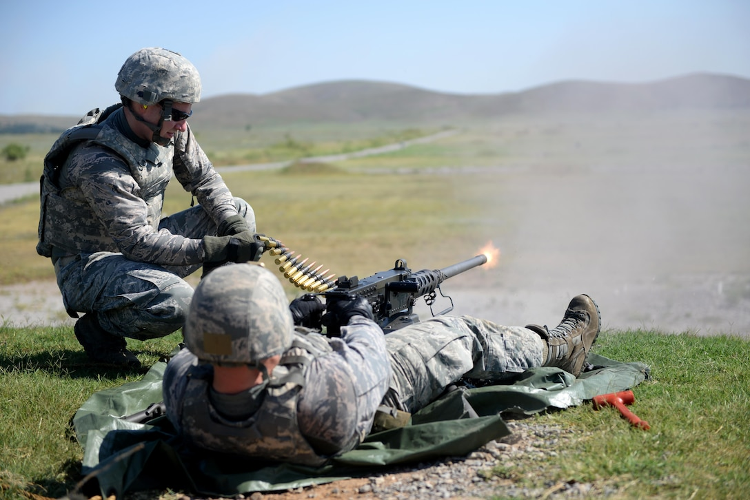U.S. Air Force Staff Sgt. Joseph Sewell, 97th Security Forces Squadron, combat arms training and maintenance instructor, fires an M2 machine gun while U.S. Air Force Senior Airman Bradley Primmer, 82nd SFS CATM instructor from Sheppard Air Force Base, Texas, feeds munitions to the weapon at the Kerr Hill Machine Gun Range, Aug. 7, 2015. Members from the 97th SFS and 82nd SFS trained together to qualify and maintain M2 certifications. (U.S. Air Force photo by Senior Airman Dillon Davis)