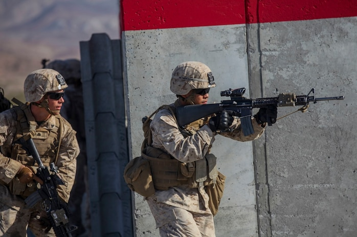 Marines with Company A, 1st Battalion, 7th Marine Regiment, move at the alert in between buildings during a Military Operation on Urban Terrain exercise aboard Marine Corps Air Ground Combat Center Twentynine Palms, California, Aug. 11, 2015. The MOUT exercise was part of an Integrated Training Exercise that allowed the Marines with Animal Company to showcase their different capabilities in preparation for future deployments.