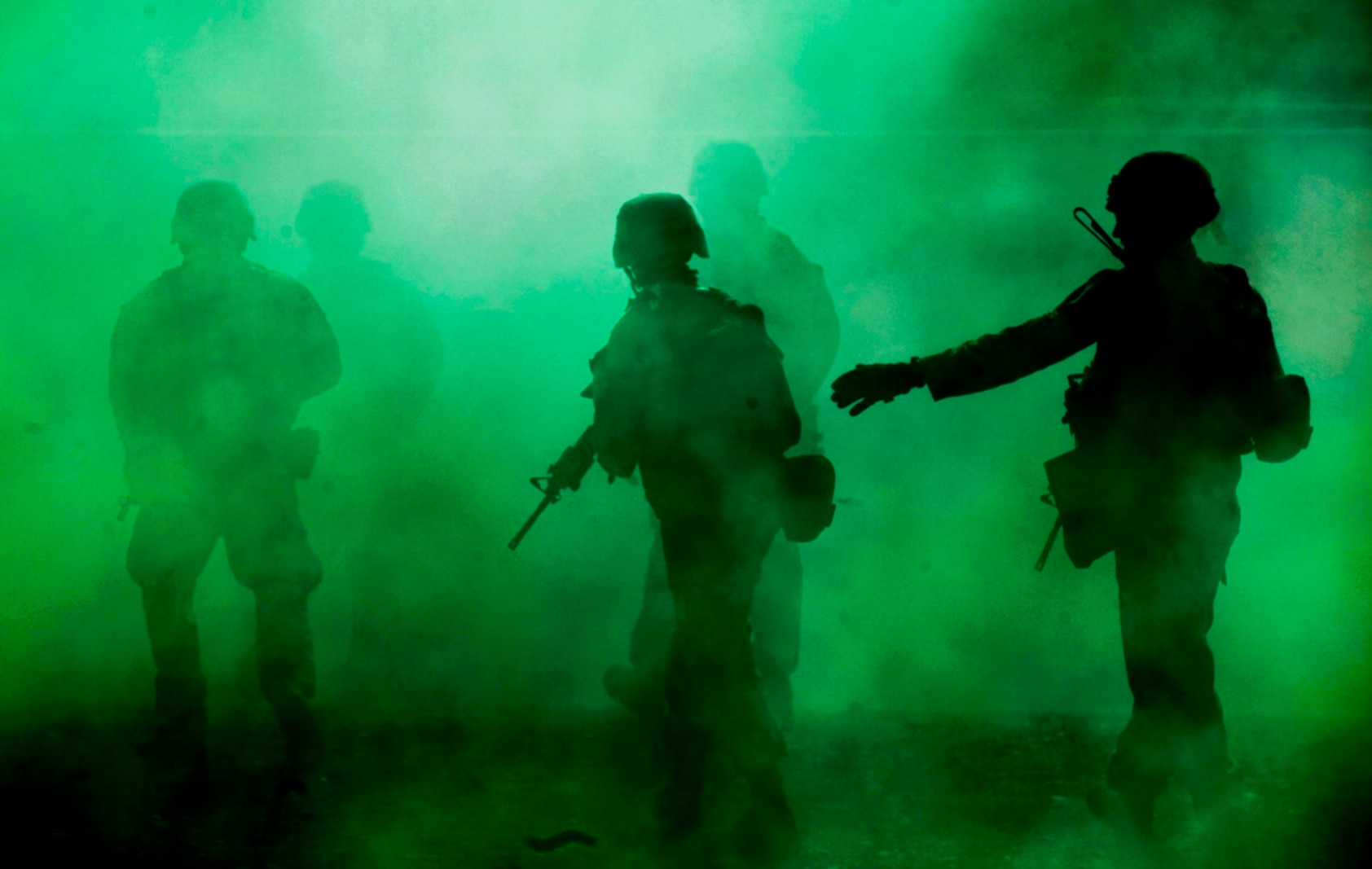 Marines with Company A, 1st Battalion, 7th Marine Regiment, use green smoke to provide concealment as they move through the simulated town during a Military Operation on Urban Terrain exercise aboard Marine Corps Air Ground Combat Center Twentynine Palms, California, Aug. 11, 2015. The MOUT exercise was part of an Integrated Training Exercise that allowed the Marines with Animal Company to showcase their different capabilities in preparation for future deployments.