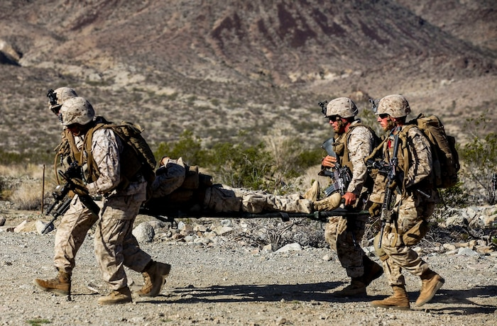 Marines and Corpsman with Company A, 1st Battalion, 7th Marine Regiment, evacuate a simulated casualty during a Military Operation on Urban Terrain exercise aboard Marine Corps Air Ground Combat Center Twentynine Palms, California, Aug. 11, 2015. The MOUT exercise was part of an Integrated Training Exercise held to evaluate unit performances in preparation for future deployments.