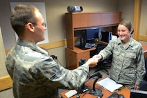 U.S. Air Force Senior Airman Alicia Lyons, a 354th Force Support Squadron career development journeyman, hands a customer his military common access card, Aug. 11, 2015, at Eielson Air Force Base, Alaska. Lyons is trained on multiple personnel sections throughout her squadron. (U.S. Air Force photo by Senior Airman Ashley Nicole Taylor/Released)