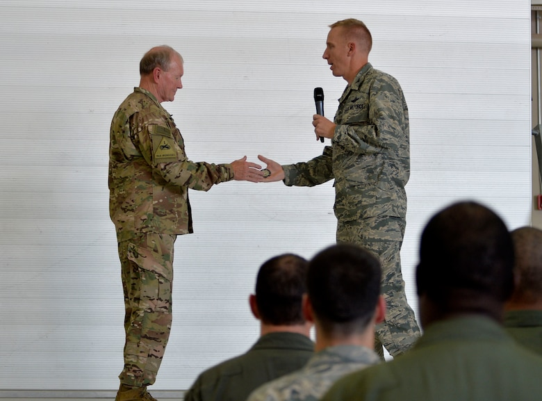 Col. Case Cunningham, 432nd Wing/432nd Air Expeditionary Wing Public Affairs presents a coin to Army Gen. Martin E. Dempsey, Chairman of the Joint Chiefs of Staff speaks after an all-call on Aug. 12, 2015, at Creech Air Force Base, Nevada. During his visit to Creech AFB, Dempsey and his wife Deanie toured the base to ask the Creech Airmen questions. (U.S. Air Force photo by Airman 1st Class Christian Clausen/Released)