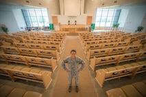 U.S. Air Force Staff Sgt. Jen Vahalik, the 354th Fighter Wing NCO in-charge of chapel plans and programs, stops work for a brief photo July 29, 2015, in the Base Chapel at Eielson Air Force Base, Alaska. Vahalik said the favorite part of her job is being able to help and encourage Airmen and their families. (U.S. Air Force photo by Staff Sgt. Shawn Nickel/Released)