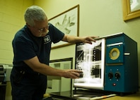 John Sanders, a contractor with the 57th Maintanence Group, looks at a film x-ray of an aircraft at the Nondestructive Inspection Laboratory on Nellis Air Force Base, Nev., Aug. 11, 2015. The NDI Lab utilizes x-rays to pin-point possible damage to aircraft components.(U.S. Air Force photo by Airman 1st Class Rachel Loftis)