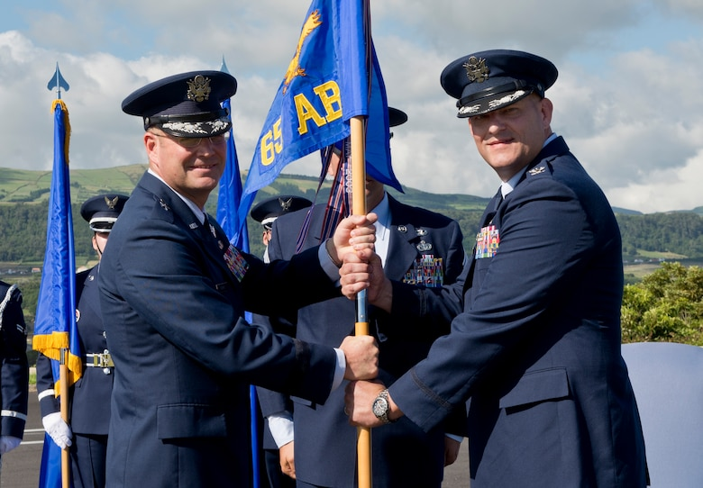 Col. Richard Sheffe, commander of the 65th Air Base Group, receives the guidon from Brig. Gen. Jon Thomas, commander of the 86th Airlift Wing, Ramstein Air Base, Germany. Sheffe assumes command of the 65th Air Base Group during a Redesignation Ceremony on Lajes Field, Azores, Portugal, August 14, 2015. With this Redesignation Ceremony, the 65th Air Base Group is now aligned under the 86th Airlift Wing and remains positioned to provide agile combat support and services to aircraft and aircrews. (U.S. Air Force photo by Master Sgt. Bradley C. Church)