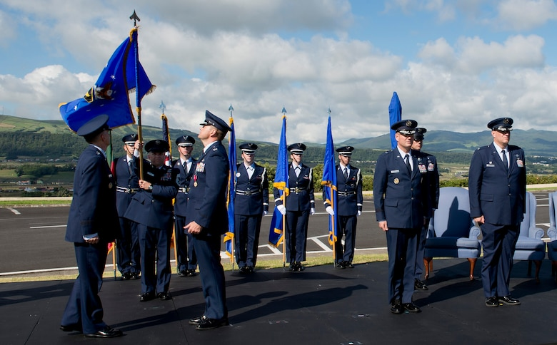 Chief Master Sgt. John Storms, superintendent of the 65th Mission Support Group, lowers the 65th Air Base Wing flag to be furled during a Redesignation Ceremony on Lajes Field, Azores, Portugal, August 14, 2015. With this Redesignation Ceremony the 65th Air Base Group is now aligned under the 86th Airlift Wing and remains positioned to provide agile combat support and services to aircraft and aircrews.  (U.S. Air Force photo by Master Sgt. Bradley C. Church)