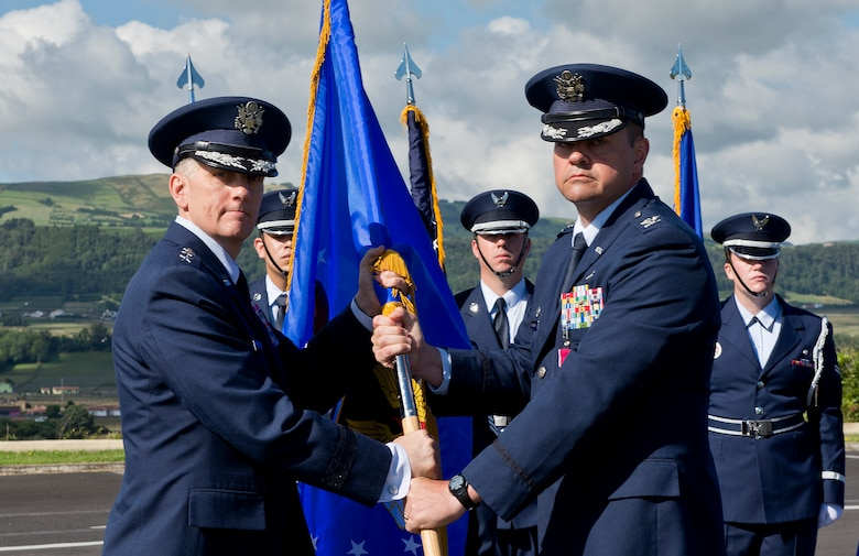 Col. Martin Rothrock, commander of the 65th Air Base Wing, passes the guidon to Lt. Gen. Timothy Ray, commander of the Third Air Force and 17th Expeditionary Air Force, relinquishing command during a Redesignation Ceremony on Lajes Field, Azores, Portugal, August 14, 2015. With this Redesignation Ceremony the 65th Air Base Group is now aligned under the 86th Airlift Wing and remains positioned to provide agile combat support and services to aircraft and aircrews. (U.S. Air Force photo by Master Sgt. Bradley C. Church)