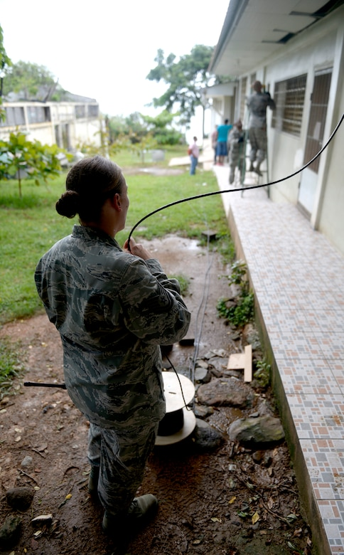 U.S. Air Force Tech Sgt. Jasmine Matus, radio frequency transmissions craftsman, provides category six cable to U.S. Air Force Tech Sgt. Carl Koenig, radio frequency transmissions technician (right) who is installing it in the roof of the Dr. Salvador Paredes Hospital in Trujillo, Honduras, June 29, 2015, with the help of U.S. Air Force Senior Airman Trenton Freeman, client systems journeyman (center). The combat communications Airmen are with the 35th Combat Communications Squadron out of Tinker Air Force Base, Okla., and were in the hospital to repair its ailing network as part of the New Horizons Honduras 2015 training exercise.   New Horizons was launched in the 1980s and is an annual joint humanitarian assistance exercise that U.S. Southern Command conducts with a partner nation in Central America, South America or the Caribbean. The exercise improves joint training readiness of U.S. and partner nation civil engineers, medical professionals and support personnel through humanitarian assistance activities. (U.S. Air Force photo by Capt. David J. Murphy/Released)