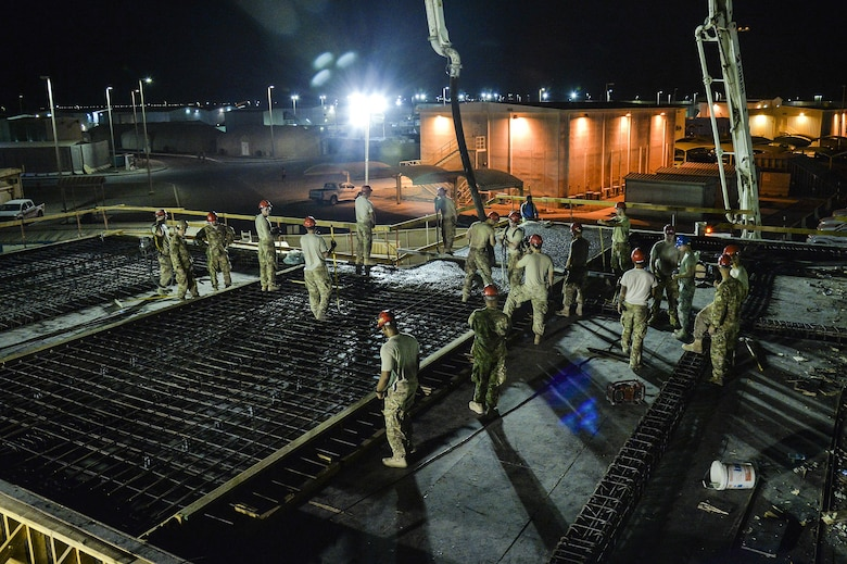 Airmen assigned to the 557th Expeditionary RED HORSE Squadron pour concrete roof on a structure at an undisclosed location in Southwest Asia July 28, 2015. RED HORSE is a self-sustaining, mobile, heavy construction squadron capable of rapid response and independent operations in remote, high-threat environments worldwide. (U.S. Air Force photo/Tech. Sgt. Christopher Boitz)