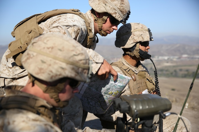 1st Lt. Mark Null (center), an artillery officer assigned to 2nd Battalion, 11th Marine Regiment, 1st Marine Division, shows coordinates to his radio operator in order to call for fire, aboard Marine Corps Base Camp Pendleton, Calif., Aug. 14, 2015. 2/11 annually conducts Summer Fire Exercise to sustain core proficiencies and to further develop their ability to execute fire missions.