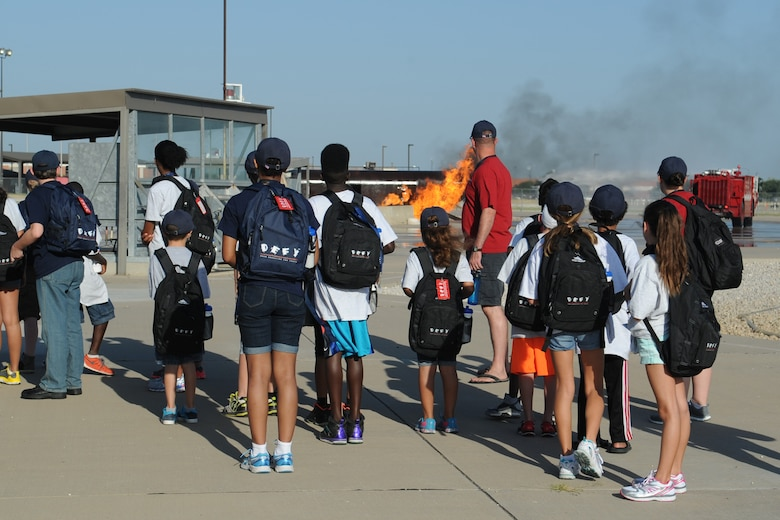 Drug Education for Youth participants watch 312th Training Squadron students put out a fire at the Louis F. Garland Department of Defense Fire Academy, Goodfellow Air Force Base, Texas, Aug. 6, 2015. The coordinators lined up several events for the children to go to, including trips to the Abilene Zoo and many more. (U.S. Air Force photo by Staff Sgt. Laura R. McFarlane/Released)