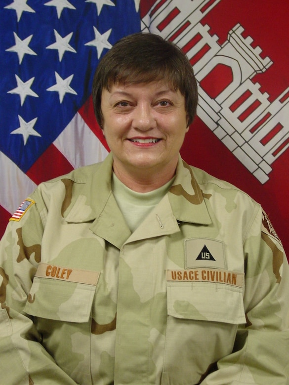 Martha Coley, pictured in her official deployment portrait, supported Operation Iraqi Freedom as a staff accountant from August 2007 to February 2008. As a Corps of Engineers employee based out of Millington, Tennessee, she often collected and sent donations to the Baghdad Division's hospitals, orphanages and schools until she was selected for direct involvement. During her six month assignment, she worked directly with construction funding and contracts, but extended time to sort donations with the Morale, Welfare and Recreation committee and collect infant clothes for the birthing center facility built in Fallujah.