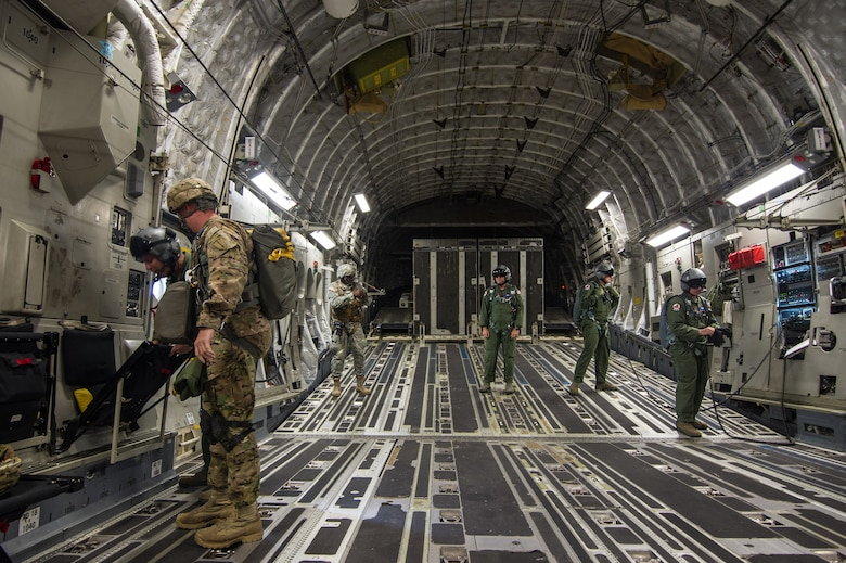 Loadmasters from the 701st Airlift Squadron at Joint Base Charleston, S.C. stand ready in a C-17 Globemaster III during a flight over Lawson Army Airfield, Fort Benning, Ga. Aug. 15, 2015. Reserve aircrews from the 701st and 300th AS flew two C-17s during Fort Benning's celebration of the 75th anniversary of the U.S. Army Airborne School. Almost 300 paratroopers took the big leap in the day's event. (U.S. Air Force photo by Staff Sgt. Bobby Pilch)
