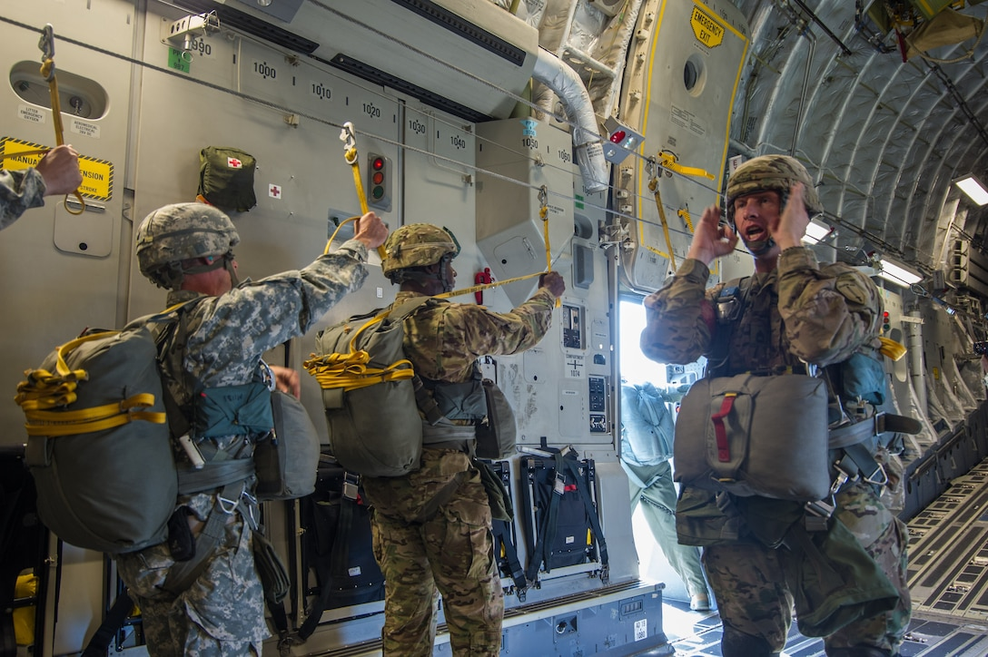U.S. Army paratroopers listen to their jump master as they prepare to jump out of a C-17 Globemaster III Aug. 15, 2015 during a flight over Lawson Army Airfield, Fort Benning, Ga. Reserve aircrews from the 701st and 300th Airlift Squadron out of Joint Base Charleston, S.C. flew two C-17s during Fort Benning's celebration of the 75th anniversary of the U.S. Army Airborne School. Almost 300 paratroopers took the big leap in the day's event. (U.S. Air Force photo by Staff Sgt. Bobby Pilch)