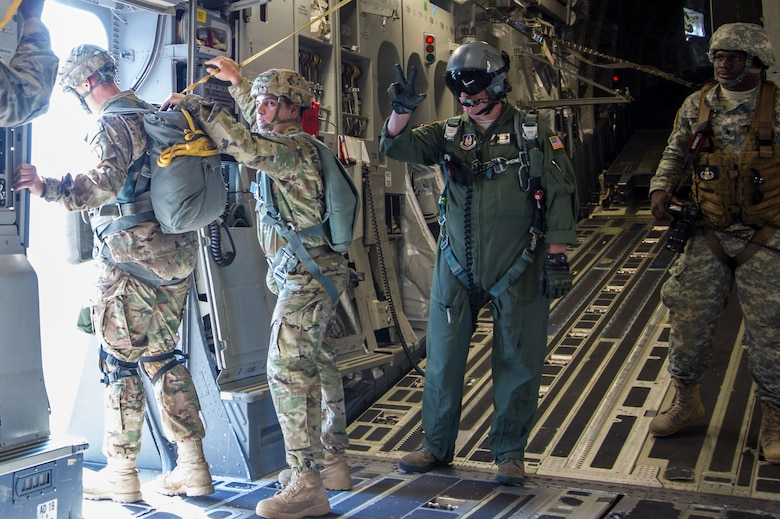 Master Sgt. Al Larson, 701st Airlift Squadron loadmaster and former U.S. Army paratrooper, communicates with hand signals during a flight over Lawson Army Airfield, Fort Benning, Ga. Aug. 15, 2015. Reserve aircrews from the 701st and 300th AS out of Joint Base Charleston, S.C. flew two C-17s during Fort Benning's celebration of the 75th anniversary of the U.S. Army Airborne School. Almost 300 paratroopers took the big leap in the day's event. (U.S. Air Force photo by Staff Sgt. Bobby Pilch)