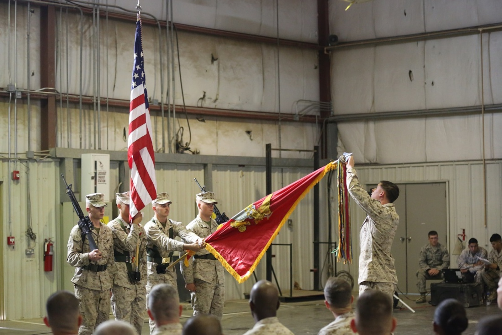 One by one, Marines with Special Purpose Marine Air Ground Task Force-Crisis Response-Central Command place a battle streamer on the Regimental Colors to symbolize the 7th Marine Regiment's unit awards during the 98th anniversary ceremony, held in an undisclosed location in Southwest Asia, Aug. 15, 2015. The 7th Marine Regiment Headquarters and 3rd Battalion, 7th Marines are currently deployed with the SPMAGTF-CR-CC and took time to remember the regiment's storied history and rededicate themselves to their current work with Operation Inherent Resolve.