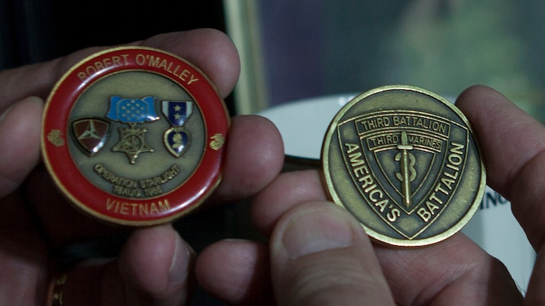 """Charles """"Charlie"""" Fink, Marine Vietnam veteran, holds specialty-made commemorative Marine Corps challenge coins June 2, 2015 at his home in Lake Butler. The coin on the left is for Marine veteran Sgt. Robert O'Malley, who was awarded the Medal of Honor for his actions during Operation Starlite."""