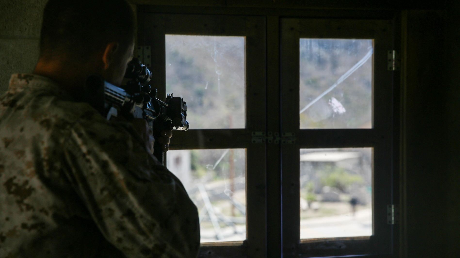 A Marine with 2nd Battalion, 7th Marine Regiment sights in on a simulated enemy during the culminating event of 1st Marine Division Schools' Urban Leaders Course at Marine Corps Base Camp Pendleton, Calif., Aug. 12, 2015. The course is a 15-day period of instruction that includes classwork, combat marksmanship and physical training executed in a simulated urban combat environment.