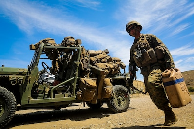 Private First Class Jonathan Meissen, a native of Parsons, Kan., and a basic rifleman with Company B, 1st Battalion, 1st Marine Regiment, unloads jugs of water off an M1161 Internally Transportable Vehicle during the first phase of a Limited Objective Experiment aboard Marine Corps Base Camp Pendleton, Calif., Aug. 13, 2015. The experiment is comprised of the integration of ITVs with infantry units to provide the Marine Corps Warfighting Laboratory with an understanding of how the vehicles will be added to the battalions. The second part of the experiment will take place at Fort Hunter Liggett, Calif., which will provide the Marines with extensive amounts of terrain to test the vehicles' capabilities over a 3-week training period. (U.S. Marine Corps Photo by Sgt. Rick Hurtado / Released)
