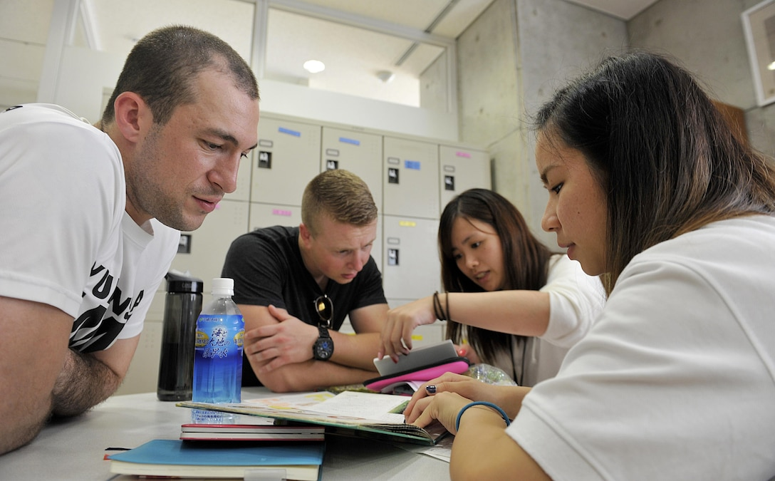 Kadena Language Institute students read a Japanese story book in English for U.S. Air Force volunteers from the 18th Wing during a culture exchange at Kadena Rotary Plaza, Japan, Aug. 14, 2015. The event was designed to help the local students improve their English skills in various situations and also aimed to deepen friendships and mutual understanding between the students and military volunteers through language, culture and activities. (U.S. Air Force photo by Naoto Anazawa/Released)