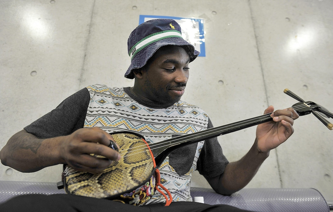 U.S. Air Force Senior Airman Kevin Inniss, 18th Communications Squadron knowledge manager, plays a Sanshin (Okinawa traditional guitar) during a culture exchange program at Kadena Rotary Plaza, Japan, Aug. 14, 2015. During the program, U.S. Air Force volunteers from the 18th Wing and Kadena Language Institute students exchanged their culture and language to improve ties between the U.S. Air Force and local community on Okinawa. (U.S. Air Force photo by Naoto Anazawa/Released)