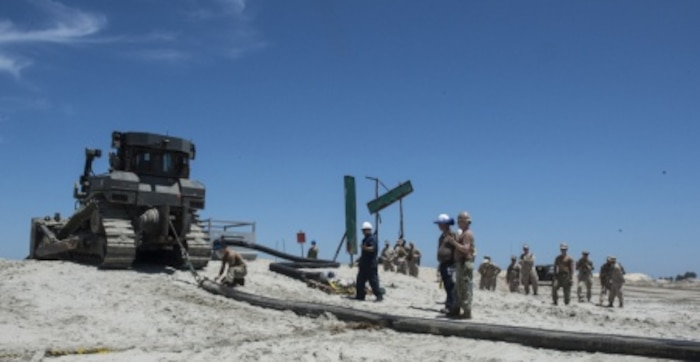 Marines with Bulk Fuel Co., 1st Marine Logistics Group, team up with Sailors from Amphibious Construction Battalion 1 to perform a beach unloading exercise using the Beach Termination Unit, in Coronado, Calif., Aug. 1-4, 2015. Approximately 30 Marines with Bulk Fuel Company, 7th Engineer Support Battalion, 1st Marine Logistics Group, teamed up with Sailors from Amphibious Construction Battalion 1 to conduct a beach unloading exercise. What made the training unique was the use of the BTU, which allows Marines to transfer fuel from a ship out in the ocean to Marines on land.