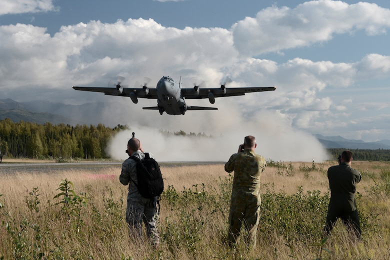 Observers watch a U.S. Air Force C-130 Hercules with the 36th Airlift Squadron from Yokota Air Base, Japan, take off of an austere runway used for training during RED FLAG-Alaska at Joint Base Elmendorf-Richardson, Alaska, Aug. 14, 2015. The training allowed C-130 aircrew to practice austere landings and take offs, combat offloads and supply drops, but also allowed friendly competition between participating Air Forces: U.S. Air Force, Japan Air Self-Defense Force, Royal Air Force, Royal Australian Air Force, Royal New Zealand Air Force and Royal Thai Air Force. Seasoned C-130 aircrew from each country judged the training exercises from the ground, allotting points based off predetermined timing and accuracy requirements. (U.S. Air Force photo by Staff Sgt. Cody H. Ramirez/Released)
