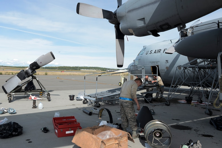 U.S. Air Force Airmen with the 374th Aircraft Maintenance Squadron refer to instructions on replacing a C-130 Hercules propeller during RED FLAG-Alaska at Joint Base Elmendorf-Richardson, Aug. 13, 2015. Maintainers, depending on the needs of the aircraft, work up to 16 hours a day to ensure the C-130 Hercules are ready for flights everyday during RFA. (U.S. Air Force photo by Staff Sgt. Cody H. Ramirez/Released)