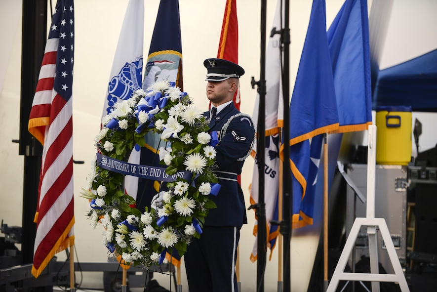 An Airman with the Air Force Honor Guard presents the wreath used in the wreath-laying ceremony at the Air Force Memorial in Arlington, Virginia, commemorating the 70th anniversary of the end of World War II, Aug. 14, 2015. The Air Force Band also put on a concert playing music from the World War II era.  (Air Force photo/Tech. Sgt. Joshua L. DeMotts)