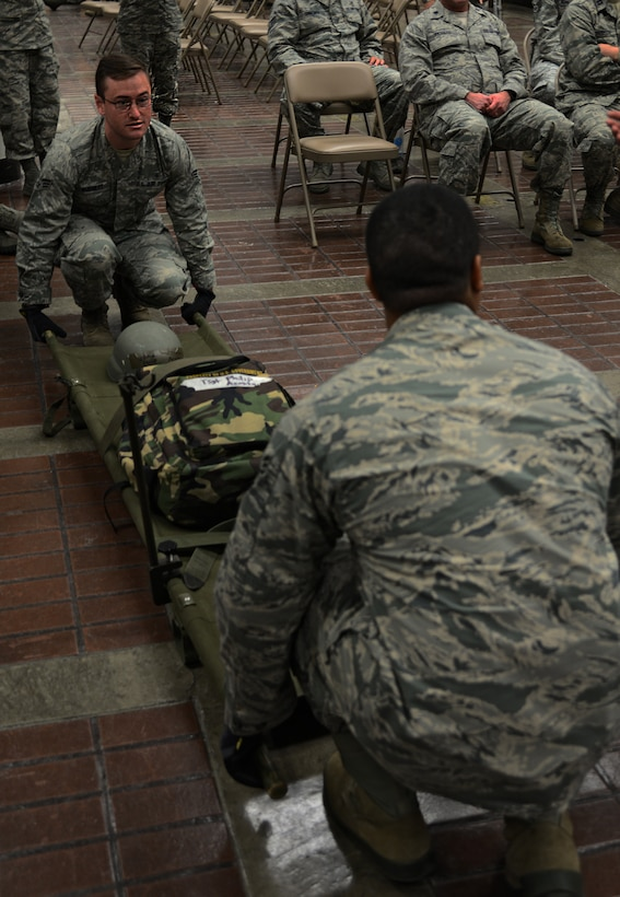 Senior Airman Timothy Burnett, 51st Aerospace Medical Squadron bio-environmental engineer and Senior Airman Jeroyd Gobert, 51st Medical Operations Squadron surgical technician, demonstrate how to lift a litter in order to place it onto a station within a patient staging area on Osan Air Base, Republic of Korea, Aug. 18, 2015.  The patient staging area is where casualties are held before they are moved to a safer location to receive follow-on care. The patient staging area can hold approximately 130 patients. (U.S. Air Force photo/Tech. Sgt. Travis Edwards)