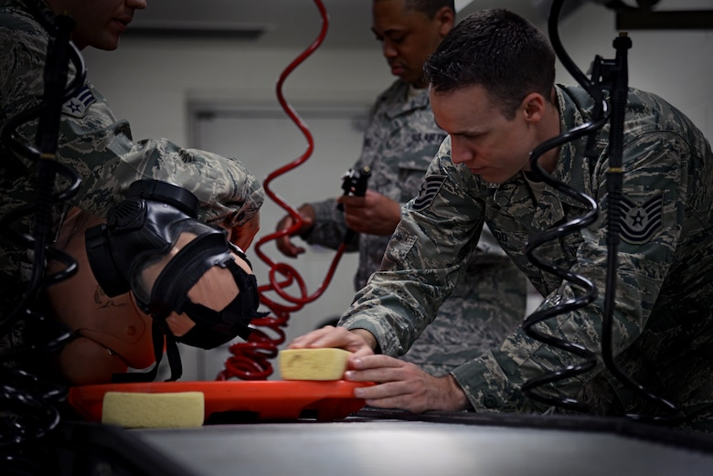 Tech. Sgt. Eric Hood, 51st Medical Operations Squadron medical decontamination instructor, demonstrates the proper way to use a sponge when decontaminating a patient on a litter on Osan Air Base, Republic of Korea, Aug. 18, 2015. The entire 51st Medical Group participated in multiple stages of readiness training to ensure the hospital and its patients would be safe from intruders and contaminants. (U.S. Air Force photo/Tech. Sgt. Travis Edwards)