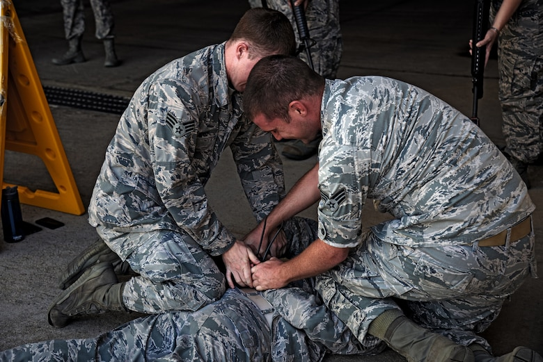 Senior Airmen Cody Murphy and William Garrett, 51st Medical Group security team members, detain a simulated uncooperative person during a training class on Osan Air Base, Republic of Korea, Aug. 18, 2015. The security team spent the day training 51st MDG members on proper security protocols and use of force prior to an impending exercise. (U.S. Air Force photo/Tech. Sgt. Travis Edwards)