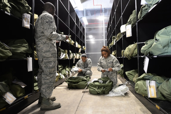 U.S. Air Force members of the 18th Logistics Readiness Squadron Material Management Flight inspect mobility bags of individual protection equipment on Kadena Air Base, Japan, Aug. 13, 2015. The 18th LRS Material Management Flight issues each Kadena Airman IPE for both training and for real-world deployments. (U.S. Air Force photo by Senior Airman Omari Bernard)
