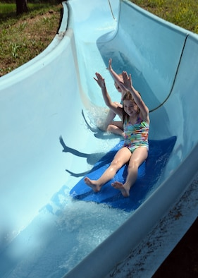 Kaley (front) and Katelyn Henneman put their hands in the air as they slide down a water slide during a 50th Space Wing Chapel-sponsored family retreat Saturday, Aug. 15, 2015, at the Horn Creek Christian Camp and Conference Grounds in Westcliffe, Colorado. The weekend retreat gave attendees the opportunity to disconnect from their electronics and focus on their family by offering activities such as horseback riding, a high ropes course, hiking, water slides, rock climbing, bowling and access to a recreation center in order to enable togetherness and family bonding. (U.S. Air Force photo/Staff Sgt. Debbie Lockhart)