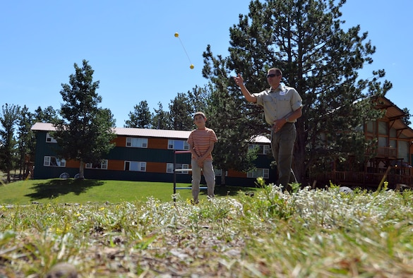 Lt. Col. Dan Burtz, 50th Operations Support Squadron commander, and his son, Mason, play a game of ladder golf during a 50th Space Wing Chapel-sponsored family retreat Saturday, Aug. 15, 2015, at the Horn Creek Christian Camp and Conference Grounds in Westcliffe, Colorado. Twenty Schriever Air Force Base families travelled more than 100 miles to spend 48 hours together with no Wi-Fi, television or other outside distractions in order to focus on family bonding and fun. (U.S. Air Force photo/Staff Sgt. Debbie Lockhart)