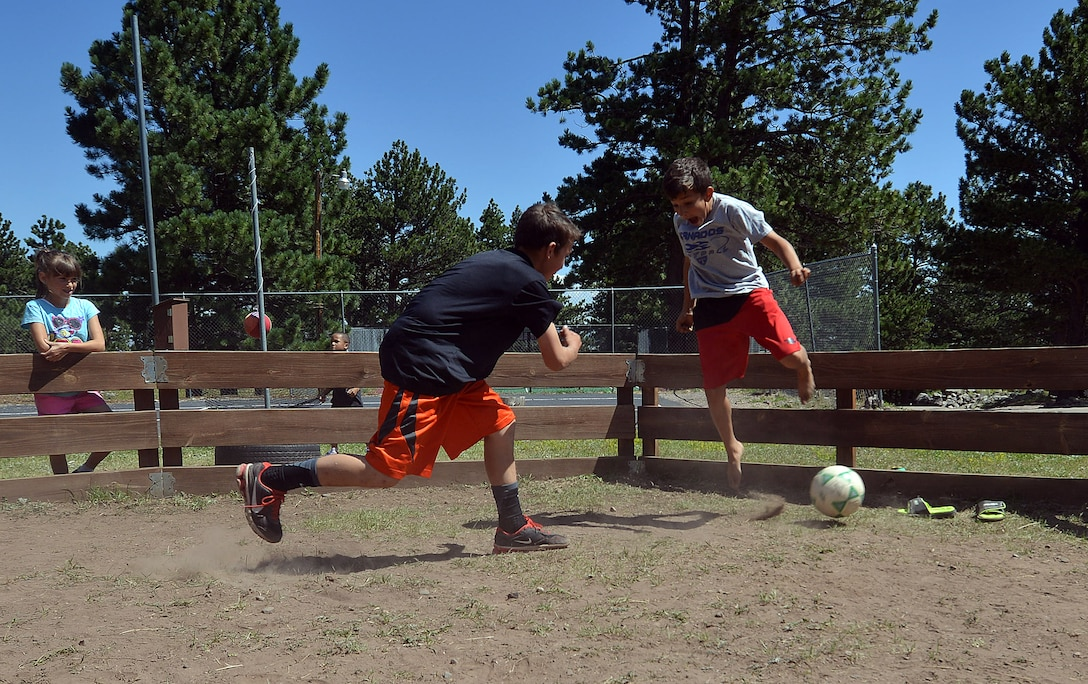 """Spencer Christiansen hits the ball toward Camrie Williams as he dodges out of the way during a """"gaga ball"""" game Saturday, Aug. 15, 2015, during a family retreat at the Horn Creek Christian Camp and Conference Grounds in Westcliffe, Colorado. Families who attended the 50th Space Wing Chapel-sponsored event also had the opportunity to participate in horseback riding, rock climbing, hiking, water slides and a ropes course. (U.S. Air Force photo/Staff Sgt. Debbie Lockhart)"""